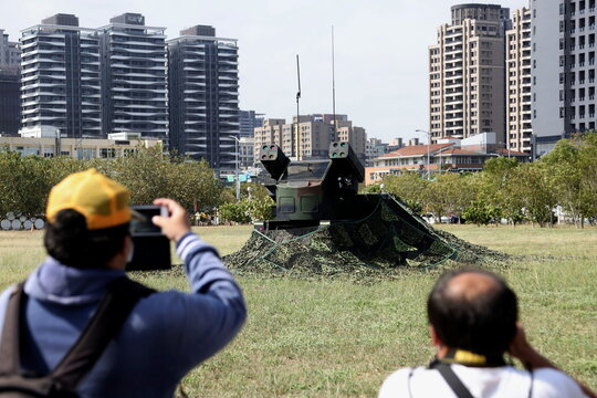 People take photos of an AN/TWQ-1 Avenger mobile air defense missile system during 'Combat Readiness Week' drills in Hsinchu,