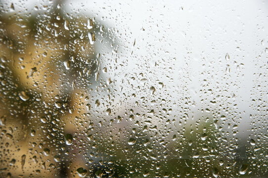 View through window with water drops at rainy weather