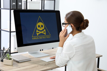 Office worker in front of computer with warning about virus attack on screen - fototapety na wymiar