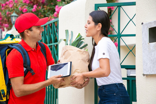 Positive female customer receiving food from grocery store, taking package from courier at her gate. Shipping or delivery service concept