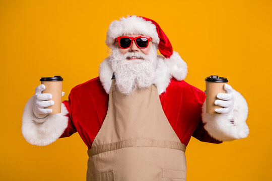 Close-up portrait of his he nice attractive cheerful cheery Santa waiter holding in hands two cups order latte beverage cacao giving order isolated bright vivid shine vibrant yellow color background