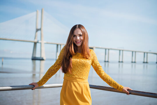 beautiful and slender girl in a yellow dress. photo and view of the big bridge. mysterious look. walking concept. rest and beauty