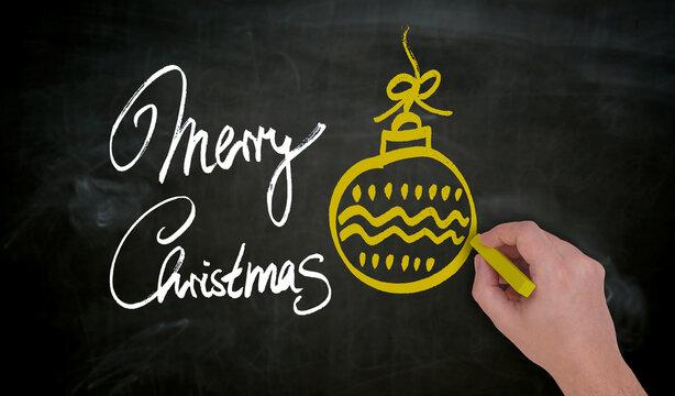 Merry Christmas wird von Hand mit Kreide auf Tafel gemalt.