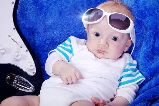 Kind sitzt cool mit E Gitarre und Brille