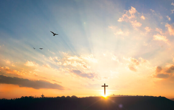 Religious concept: Silhouette cross on mountain at sunset background