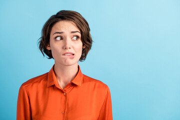 Closeup photo of sad depressed displeased lady horrified facial expression made huge big mistake feel guilty look side empty space bite lips wear orange shirt isolated blue color background Wall mural