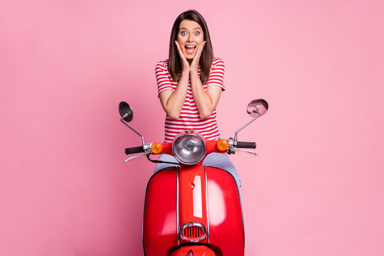 Photo portrait of female driver sitting on red motorcycle touching cheeks happily isolated on pastel pink color background