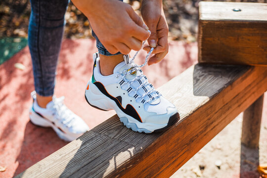 Female hands tying laces on white sneakers with black inserts standing on a wooden parapet