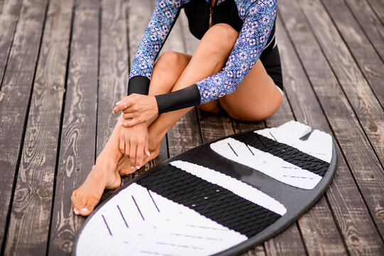 view of attractive legs and hands of woman with surf board nearby