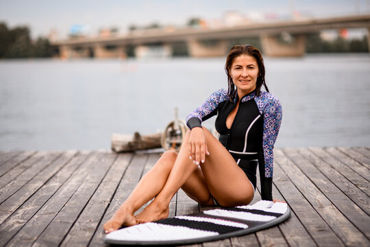 Beautiful girl in wetsuit with long fit legs sit near surf board on wooden pier