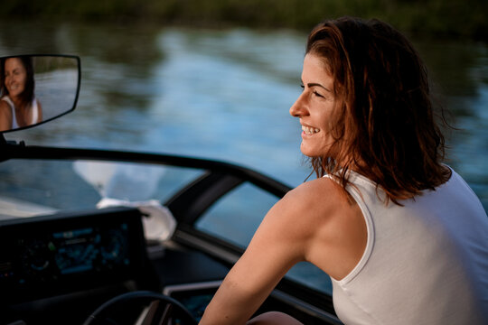 Close-up of young smiling woman sitting at the wheel of motor boat.