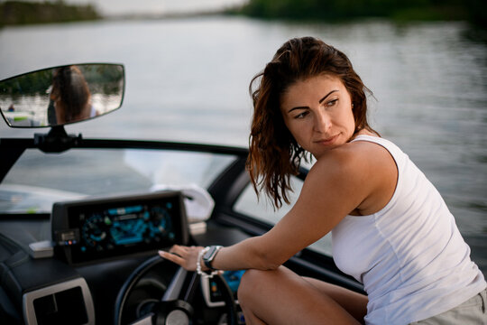 young woman is sitting at the wheel of motor boat.