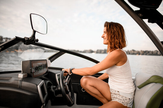 young smiling woman is sitting at the wheel of motor boat.