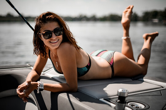 happy young attractive woman with brown hair in swimsuit and sunglasses lies on the boat.