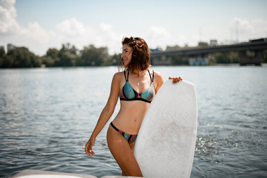 view of beautiful young woman in bright bikini with surf board with her hands