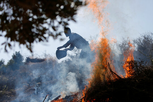 A Palestinian farmer burns grass as he cleans a field before picking up olives near the Israeli barrier in Salfit in the Israeli-occupied West Bank