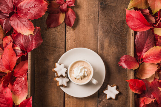 Cup of hot cappuccino or chocolate with cookies on wooden background copy space and colorful autumn leaves.
