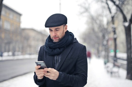 young man writes with smartphone walking in a snowy street
