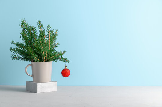 Alternative Christmas tree in gray mug decorated red ball on pastel blue background. Xmas greeting card with copy space.
