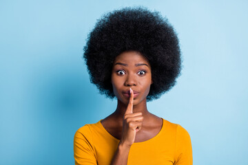 Photo portrait of black skinned girl keeping finger near lips speechless quietly isolated on...