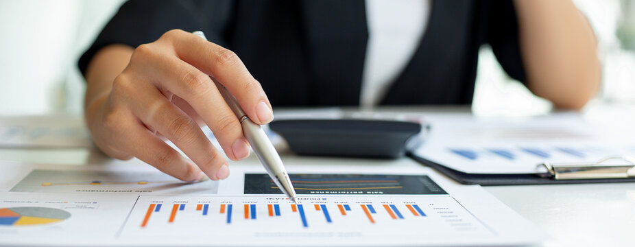 Financial Businesswomen analyze the graph of the company's performance to create profits and growth, Market research reports and income statistics, Financial and Accounting concept.