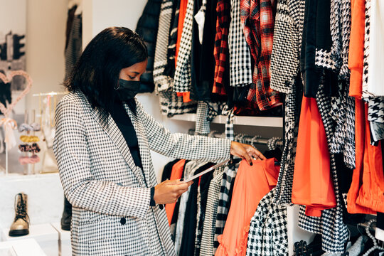 black woman manager in a fashion retail store is wearing a mask as protection against virus and using a tablet for working and checking the shop stock
