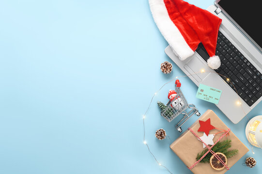 E-commerce and electronic payments concept. Christmas online shopping theme. Top view of laptop, credit card, gift box, shopping cart and Santa hat on a pastel blue background. Copy space, flat lay