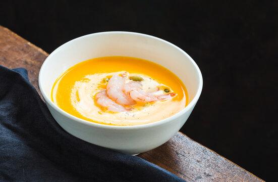 Butternut cream soup with shrimps. Vegetables gourmet healthy comfort food.