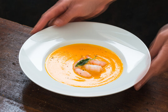 Gourmet food vegetables butternut squash cream soup with shrimps plate woman hands.
