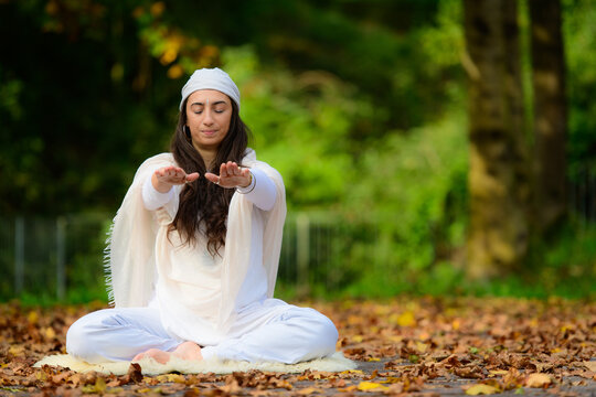 Yoga instructor practices exercises among the autumn leaves in the park