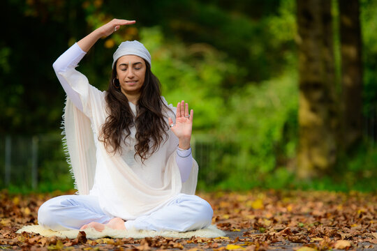 Yoga instructor practices exercises in the park in autumn
