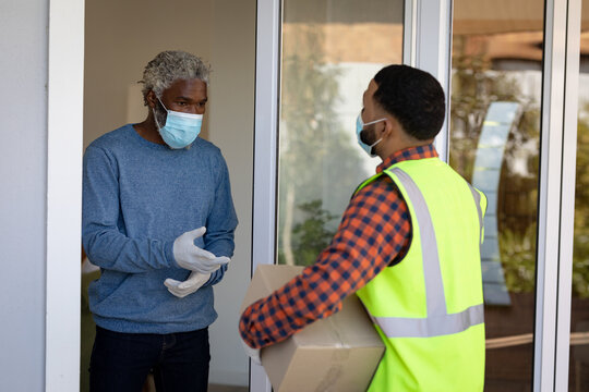 Delivery man delivering package to senior man wearing face mask at home