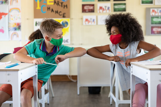 Boy and Girl wearing face masks greeting each other by touching elbows at school