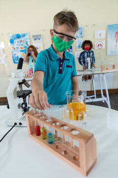Boy wearing face mask and protective glasses touching test tubes in laboratory