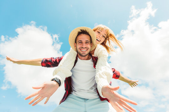 Couple in love having fun outdoor - Friends playing piggyback on a blue sky background