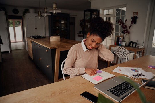 African young woman suffering from neck pain working on laptop with diary and document at home