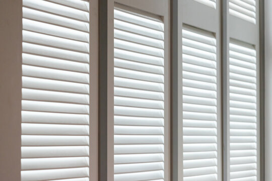 white wooden louver window decoration for vintage style. white wooden shutter with light and shadow.