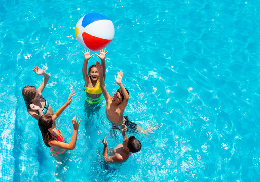 Group of kids in swimming pool play with inflatable ball view from above reaching hands up