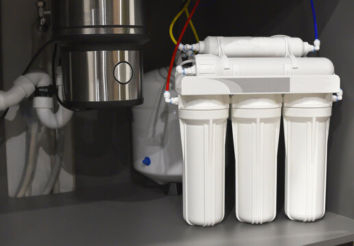 House water filtration system. Osmosis deionization system. Installation of water purification filters under kitchen sink in cupboard. Clear water concept. Small sharpness, possible granularity