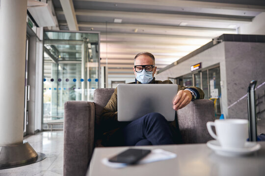 Businessman in a face mask working on his laptop