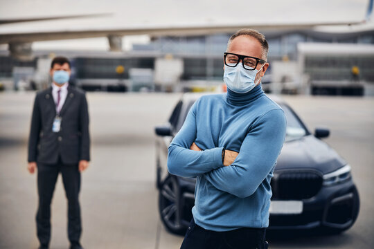 Two men in protective masks on the runway