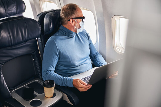 Man with a laptop looking through the airplane window