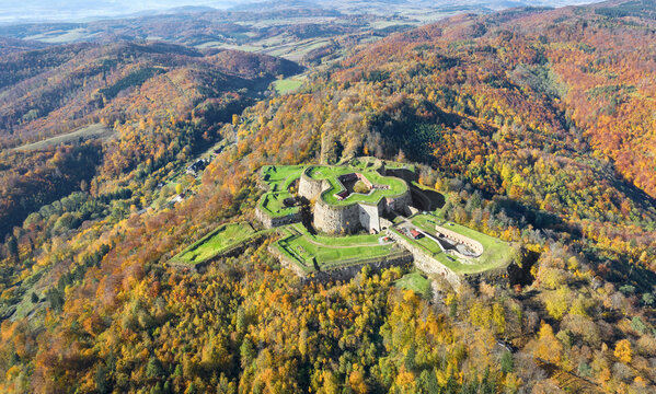 Aerial view of historic Srebrna Gora fortress surrounded by yellow autumn forest, Poland