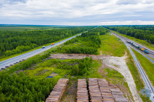 Highway road running to horizon, forest and rural housing aerial panoramic landscape.