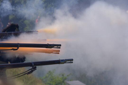 flintlock muzzle loader muskets guns firing. Smoke from the gunpowder fills the air.