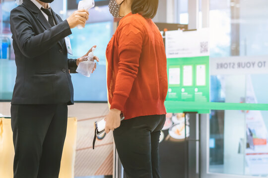 Hand of female security officer holds alcohol gel bottle to serve customers to prevent the spread of germs and bacteria and avoid infections Corona virus (Covid-19) before entering the mall.
