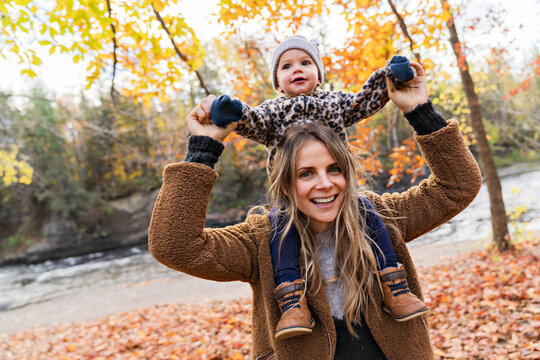 Little girl and her mother playing in the autumn park with child girl on shoulder