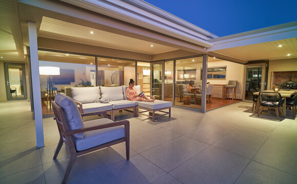 Woman relaxing with magazine on luxury home showcase patio at night