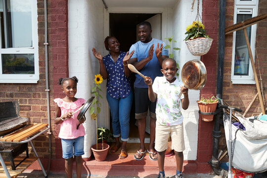 Portrait happy family celebrating with pots and pans on sunny patio