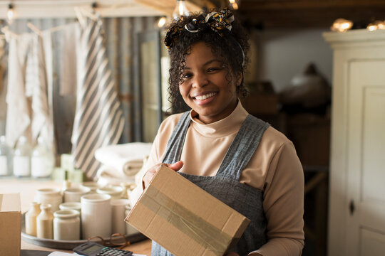 Portrait happy female shop owner with package